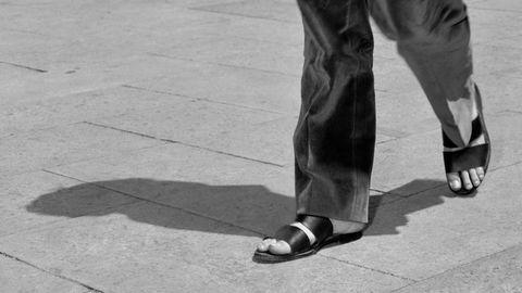 Genanse og verdighet. Den amerikanske forfatteren og levemannen Truman Capote (1924–1984) var en meget stilbevisst herre – og viser hvordan sandaler kan brukes i kombinasjon med langbukser. Her på Markusplassen i Venezia i 1951.