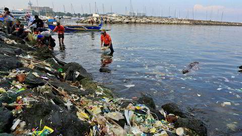 Statlig ansatte plukker og sorterer plast som har skyldt opp på strendene i Manila i Filippinene. Det største bidraget til plast i havet kommer med elver ut i sjøen.