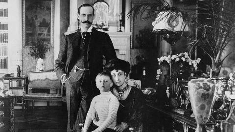 Haakon, Maud og lille Olav fotografert i 1909. Rundt dem er praktfulle og dyrebare gjenstander Maud arvet fra den britiske kongefamilien hun var en del av.