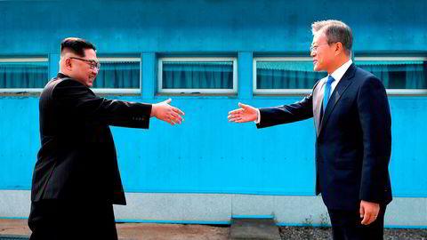 Nord-Koreas leder Kim Jong Un (t.v.) hilser på Sør-Koreas president Moon Jae-in over grenselinjen