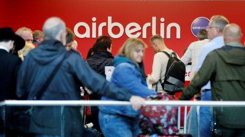 Reisende står i kø ved Air Berlins skranke på flyplassen i Düsseldorf etter at de møtte opp til en kansellert flyvning tirsdag.
