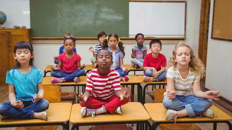 Amerikanske skole-elever mediterer i lotusstilling.