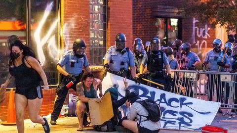 Amerikanske politifolk bruker pepperspray mot demonstranter som protesterte utenfor en politistasjon i Minneapolis 27. mai. To dager tidligere hadde 46-åringen George Floyd blitt drept av politiet i byen.