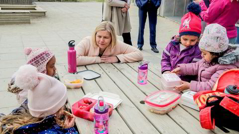 Kunnskaps- og integreringsminister Guri Melby snakker med barn i Ammerudlia barnehage som spiser. Snart vil Stortinget etablere et nasjonalt tilsyn som skal føre kontrollen med de private barnehagene i stedet for kommunene, men flere er skeptiske til ordningen.