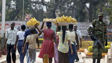 FILE PHOTO: Women carry baskets of banana as they walk past a military personnel patrolling in Kampala, Uganda February 19, 2016. REUTERS/James Akena/File Photo ---