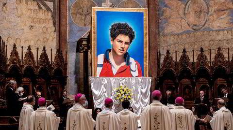 Kanskje snart helgen. Det har lenge vært en bekymring i katolske miljøer over at helgendyrkelsen vil forsvinne. Med en ny og ung helgen for internettet, skal det endre seg. Et veggteppe av Carlo Acutis henger her under saligkåringen av ham 10. oktober i Assisi, Italia.