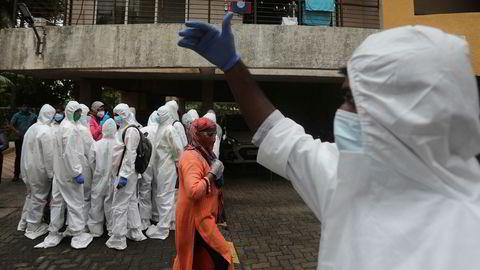 Helsearbeidere på vei inn i en boligblokk i Mumbai for å utføre korona-tester. India er verdens tredje hardest rammede land.