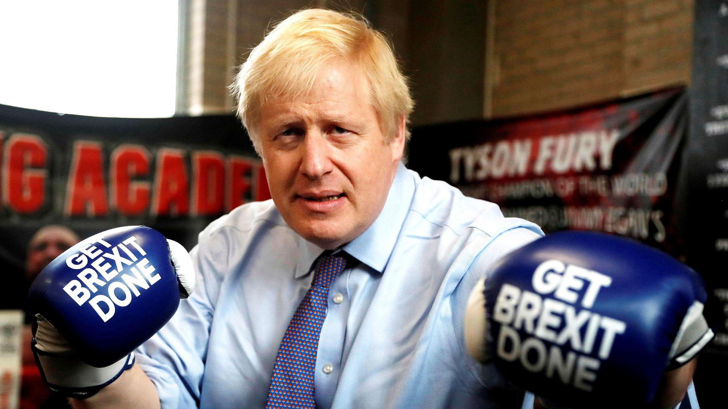 Statsminister Boris Johnson poserer med boksehansker utstyrt med «Get brexit done» under et valgkampstopp i en bokseklubb i Manchester.