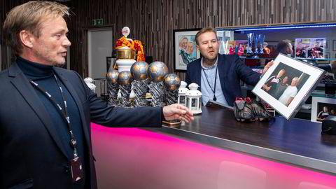 Fotballinteressen står sentralt som kulturbygger hos Ruta entreprenør. Her viser daglig leder Rune Storm (til venstre) og medgründer Hans Tarjei Finsrud frem bildet fra møtet med Liverpool-spilleren Steven Gerrard i Ruta bar, mens de gamle støvlene til Jamie Redknapp ligger på bardisken.