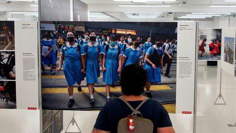 """En besøkende på utstillingen """"The 2020 World Press Photo Contest"""" ser på de prisbelønte bildene fra regjeringskritiske demonstrasjoner i Hongkong, 2019."""