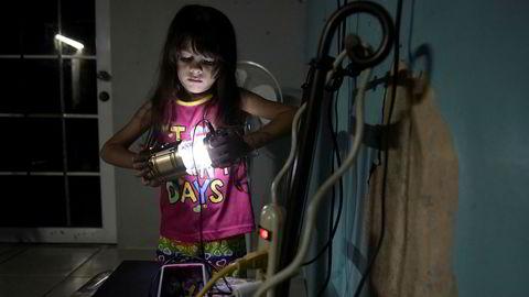 Seks år gamle Melanie Oliveras Gonzalez holder en lanterne inne i stuen der hun og familien bor i Morovis i Puerto Rico. Halvparten av landets strømkunder er fortsatt uten strøm, tre måneder etter at orkanen Maria traff øya.