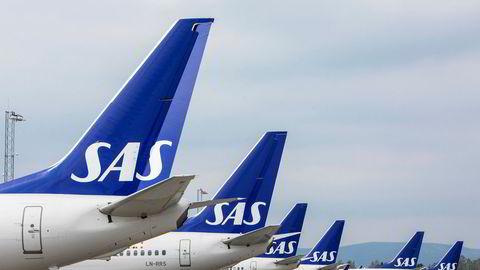 SAS-fly på rekke og rad på bakken ved Gardermoen. Ledelsen i flyselskapet hadde fredag møte med regjeringen om nye tiltak for luftfarten