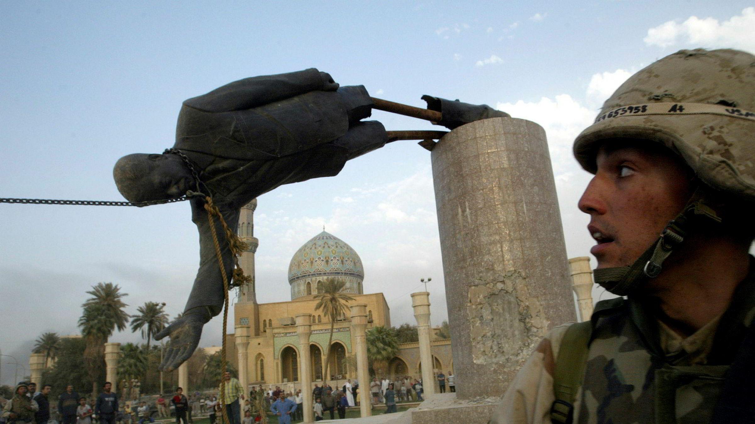 Amerikanske soldater ser på at en statue av Iraks tidligere president Saddam Hussein faller i Bagdad 9. april 2003.