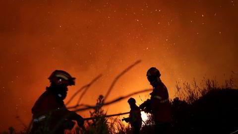 Brannmannskap i Portugal forsøker å slukke en brann ved Obidos, Portugal tidlig mandag morgen.