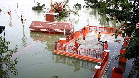 Mange er døde etter store oversvømmelser i India. På bildet står prester på taket av et oversvømmet tempel nær Sangam i Allahabad.