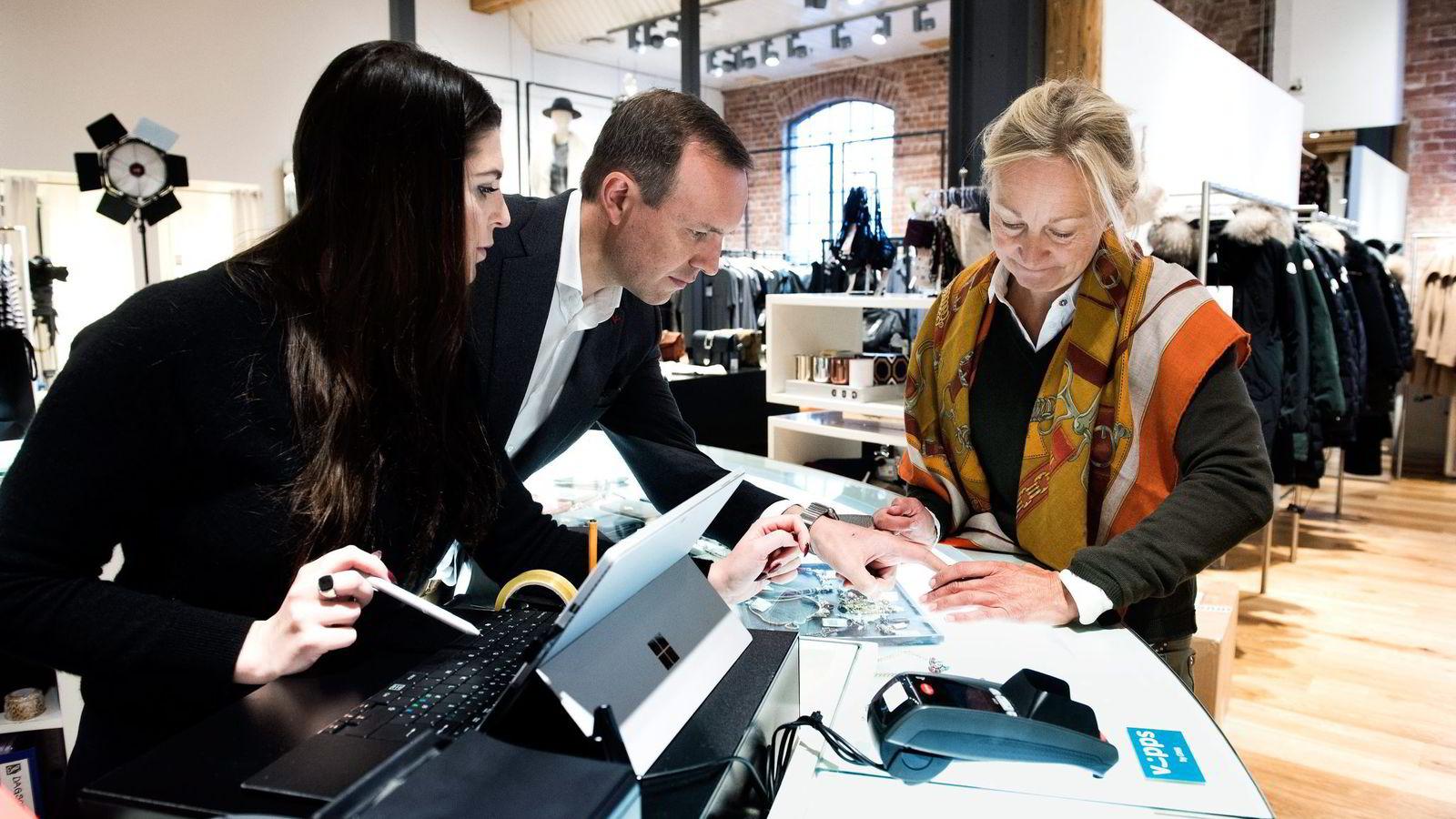 Hos klesbutikken Høyer betaler Bente Holby (til høyre) for nye sko og genser med mobilappen Vipps. Butikkmedarbeider Isabel Soler opplever at kundene er positive, og Høyers finansdirektør Inge Nygaard vil ha teknologien i alle butikker.