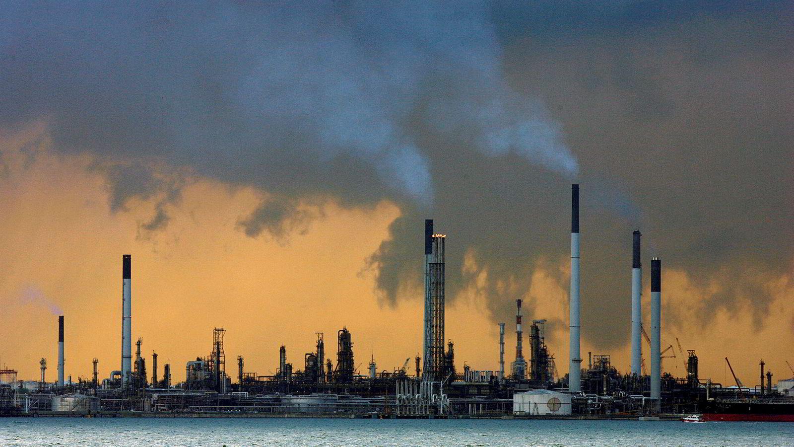 Røyk stiger ut av pipene fra et oljeraffineri ved kysten i Singapore.