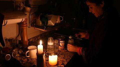 Uruguay og Argentina ble rammet av et omfattende strømbrudd søndag, her bruker en kvinne stearinlys mens hun lager mat i Motevideo, hovedstaden i Uruguay.