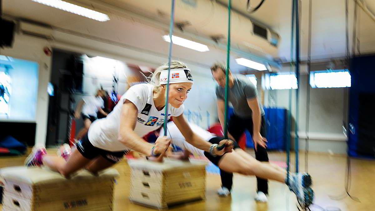 Therese Johaug styrker musklene med eksplosiv trening i slynger. Slik skal konkurrente gruses. Marit Bjørgen og Olympiatoppens Mathias Lilleheim i bakgrunnen.