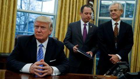 President Donald Trump og handelsrådgiver Peter Navarro (til høyre) har vært uvanlig rause med omtalen valutasvingninger etter innsettelsen. Her sammen med stabsjef Reince Priebus i Det hvite hus 23. januar i år.