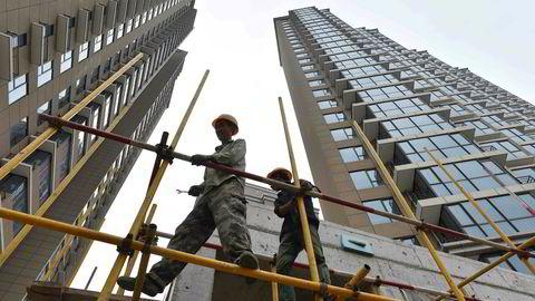 Arbeidere jobber på et nytt boligkompleks i Beijing. Både leie og kjøp er svært dyrt, sammenlignet med lokale inntekter.