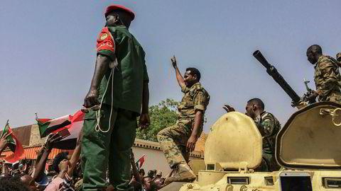Militære styrker feirer etter at president Omar al-Bashir ble tvunget til å tre tilbake etter 30 år ved makten i Sudan.