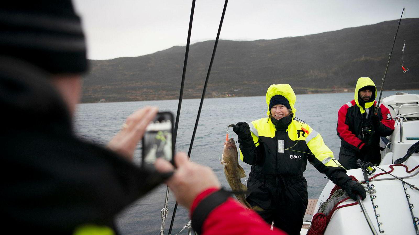 Steve Brown fra Texas tar bilde av kona Laura Brown, som akkurat har halt opp en torsk fra en av Pukka Travels seilkatamaraner i Kvalsundet nord for Tromsø. Turist Jose Galdon (til høyre) fikk ingen fisk.