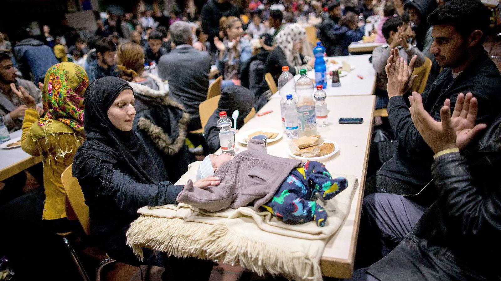 En kvinne med en liten baby er blant flyktninger som blir ønsket velkommen i Dortmund, Tyskland. Foto: Maja Hitij, AFP/NTB Scanpix