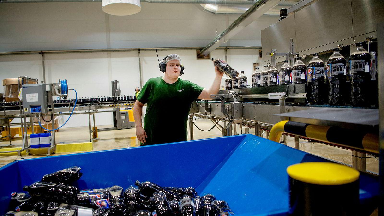Ringnes har satset tungt på sukkerfri brus og ønsker avgiftslettelse på brus uten sukker. Her sjekker lærling Simon Iversen flaskene på Ringnes-fabrikken på Gjelleråsen.