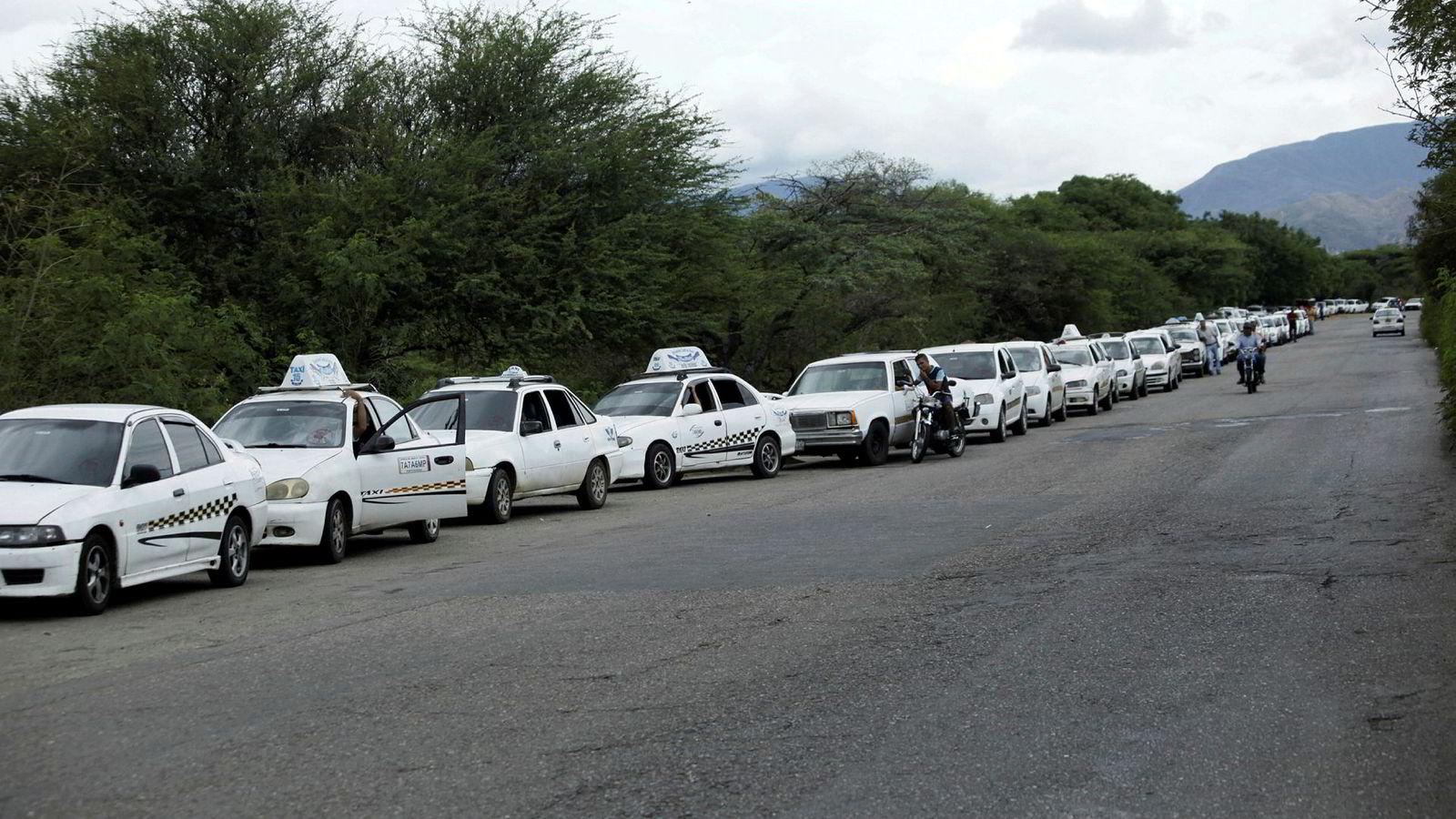 13 latinamerikanske land ber Venezuela erkjenne at landet er i en krise og trenger hjelp. Bildet viser en enorm bilkø tirsdag som venter på å komme frem til en bensinstasjon i byen San Antonio.