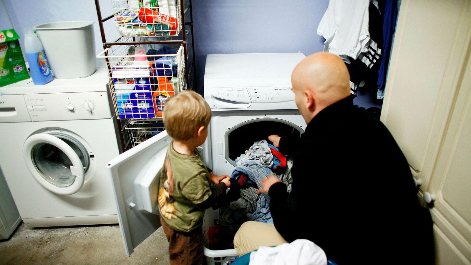 OSLO 200712 17: Far vasker tøy. Vaskekjeller. Gutt følger med. Far og sønn. Mann og barn. Husarbeid. Enslig far. Vaskemaskin. Alenepappa. Foto: Sara Johannessen / SCANPIX NB! Modellklarert ---