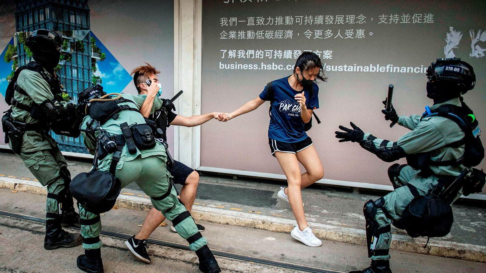 Politiet forfølger og pågriper et ungt par med ansiktsmasker i sentrum av Hongkong lørdag, et døgn etter at byens ledelse la ned forbud mot å dekke til ansiktet. Forbudet la ingen demper på Hongkong-demonstrasjonene. Tog og t-baner sto stille, og butikker holdt stengt som følge av demonstrasjonene lørdag.