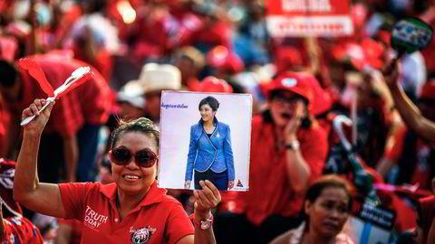 VISER STØTTE. Et medlem av «rødskjortene» holder opp et bilde av Thailands statsminister Yingluck Shinawatra under en demonstrasjon utenfor Bangkok igår. Foto: Athit Perawongmetha, Reuters/NTB Scanpix