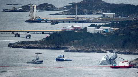 Fregatten KNM «Helge Ingstad» ligger med slagside nær Stureterminalen, som man ser i bakgrunnen.