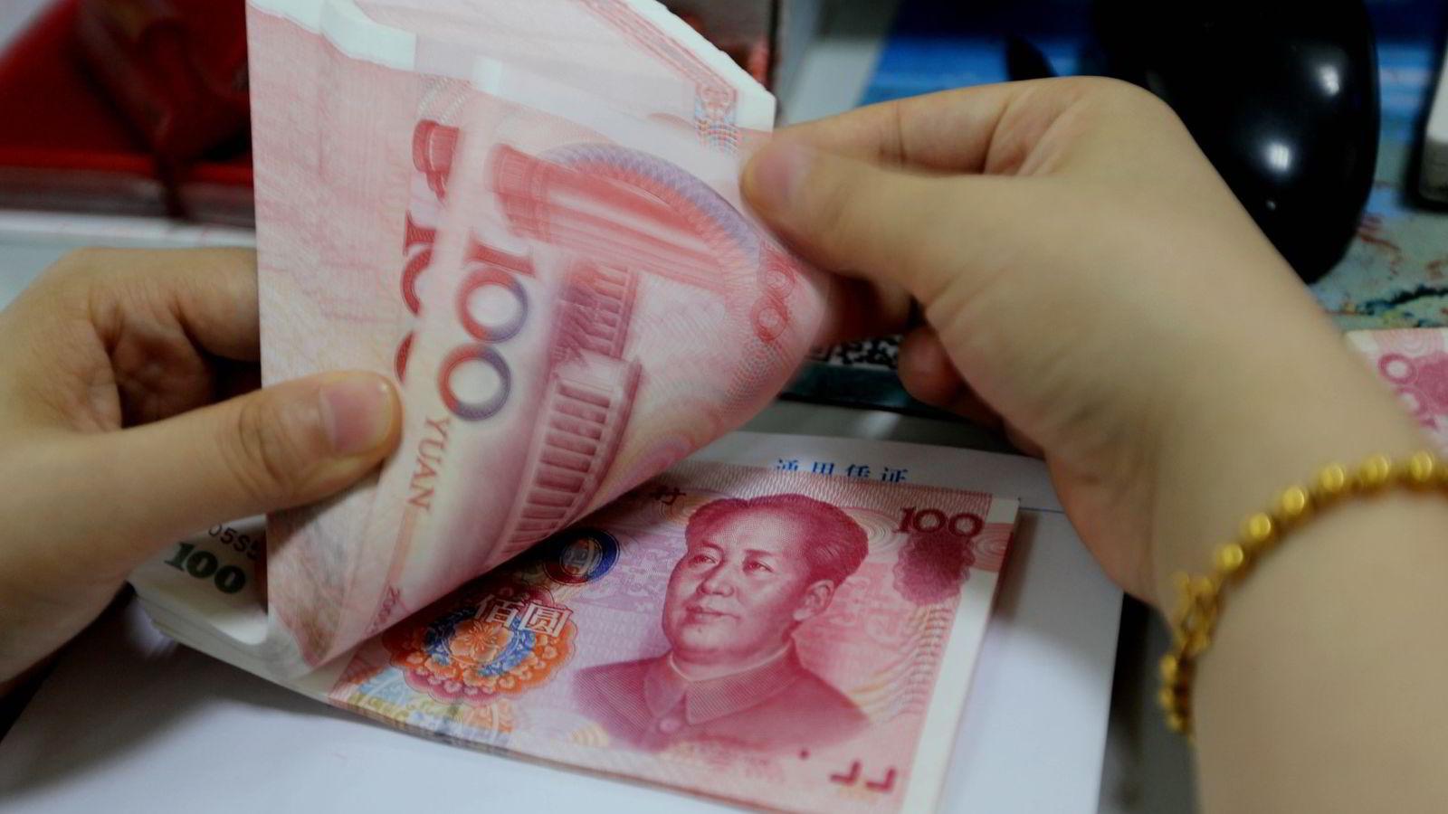 En bankansatt teller kinesiske Yuan-sedler i en filial i Lianyungang i Jiangsu-provinsen. Foto: China out/AFP photo/NTB scanpix