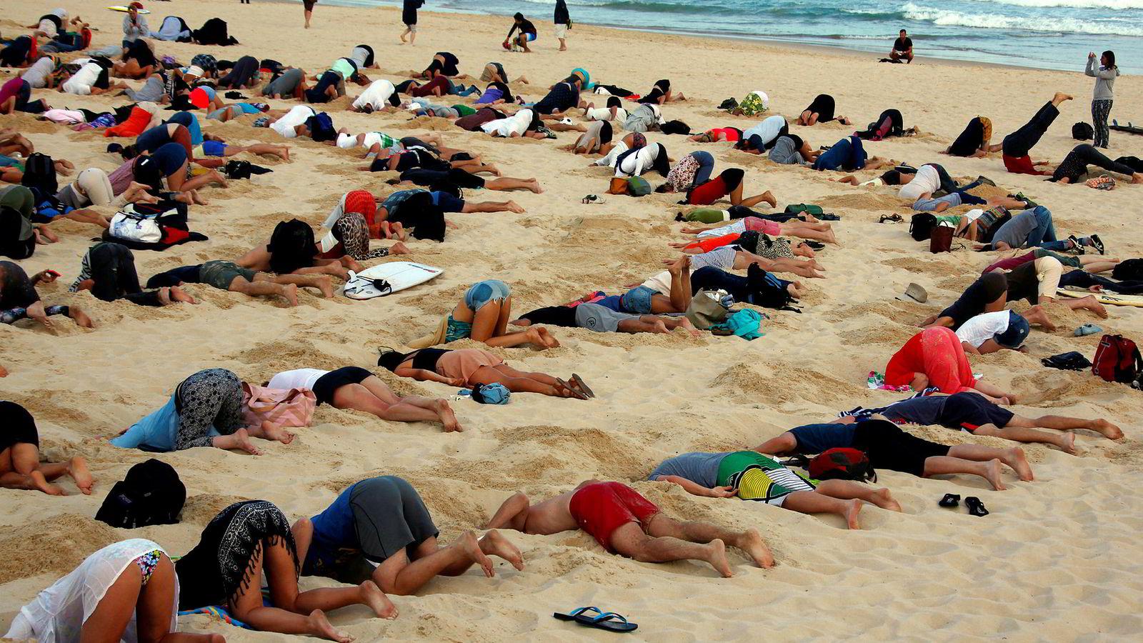 Dyster rapport om helsekonsekvenser av klimaendringene. Bildet viser en gruppe på rundt 400 demonstranter som på den berømte stranden Bondi Beach i Sydney for få år siden på en billedlig måte sa fra om at den australske regjeringen stakk hodet i sanden om klimaendringene.