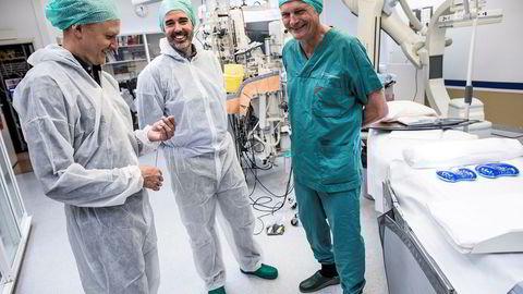 Operasjonell leder Jonas Tyssø holder sensoren som har en diameter på to millimeter og festes på hjertet etter operasjoner, flankert av daglig leder Shane West, og Erik Fosse, professor, gründer og styreleder.