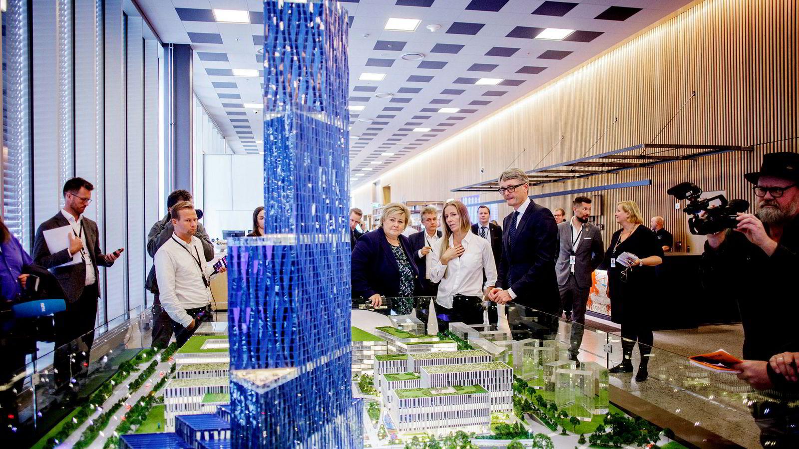 Statsminister Erna Solberg står og ser på det som kanskje blir Norges høyeste bygning, Kjell Inge Røkkes «Verdenshavenes hovedkvarter». Her står hun ved siden av Nina Jensen i Rev Ocean og konsernsjef i Aker, Øyvind Eriksen.