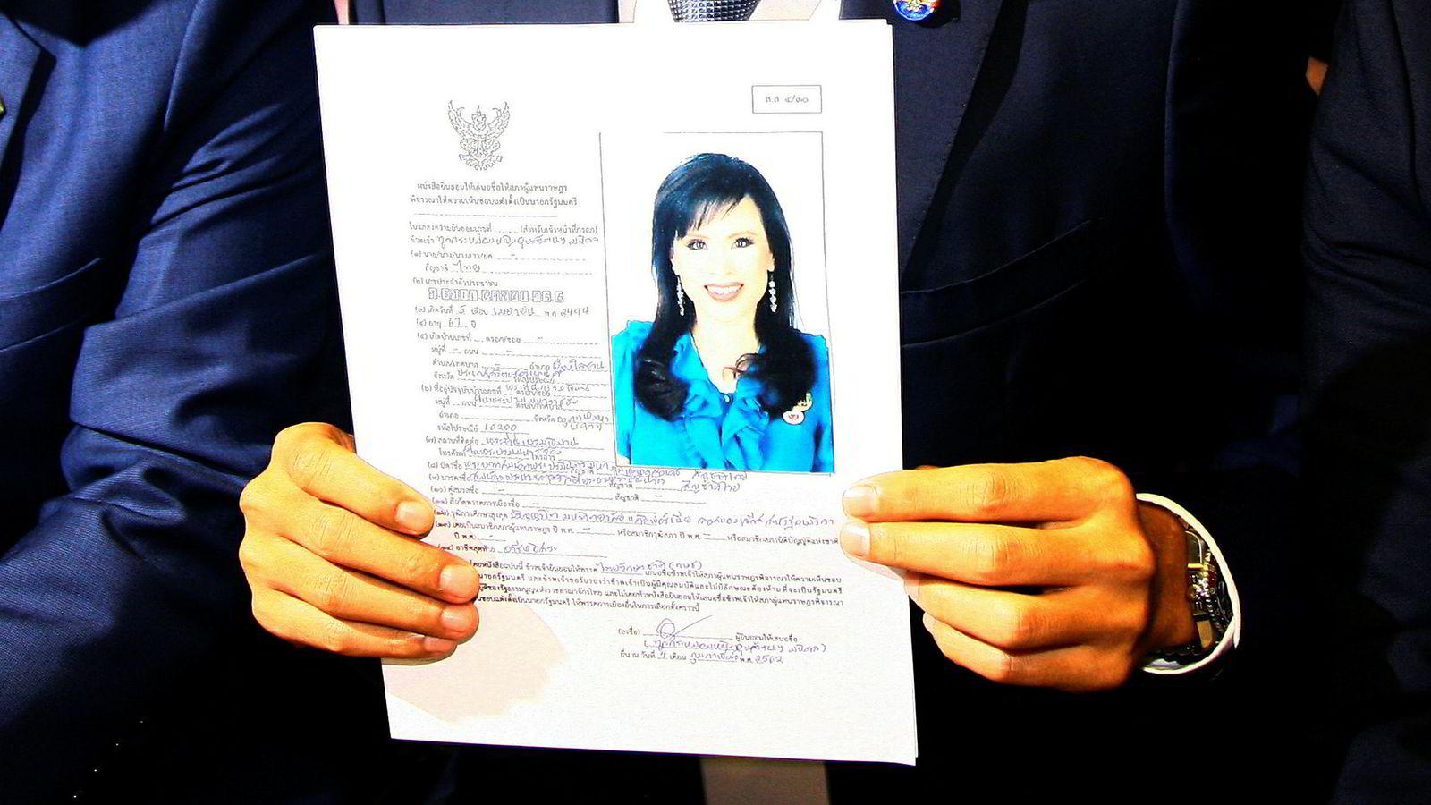 Fredag nominerte partiet Thai Raksa Chart prinsesse Ubolratana til statsministerkandidat, noe som ikke falt i god jord hos den sittende kong Maha Vajiralongkorn. Her holder partiets leder opp et bilde av prinsessen.
