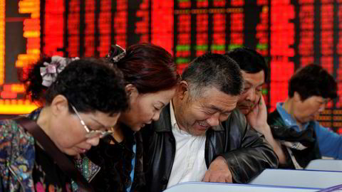 KINA: Investorer sjekker aksjekurser hos et meglerhus i Fuyang i Anhui-provinsen. Foto: China Daily/Reuters/NTB scanpix