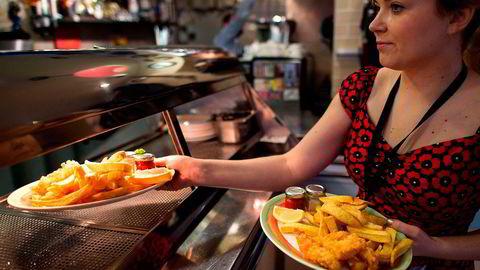 Fredag trer en ny lov i kraft i Storbritannia som setter minimumslønnen til 7,20 pund i timen. Her leverer en servitør i Øst-London ut fish and chips. Foto: AFP/Leon Neal/NTB Scanpix