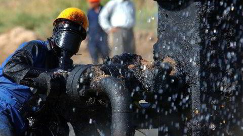 En oljearbeider prøver å stenge av en brennende oljerørledning nær en landsby utenfor Bagdad i Irak.