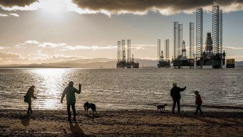 Flere rigger ligger i opplag i bakgrunnen, men folk som bor her I Cromarty i Skottland er vant til dem. Beti Bricelj, Mike Schroeder og Leon Patchett, går tur langs stranden.