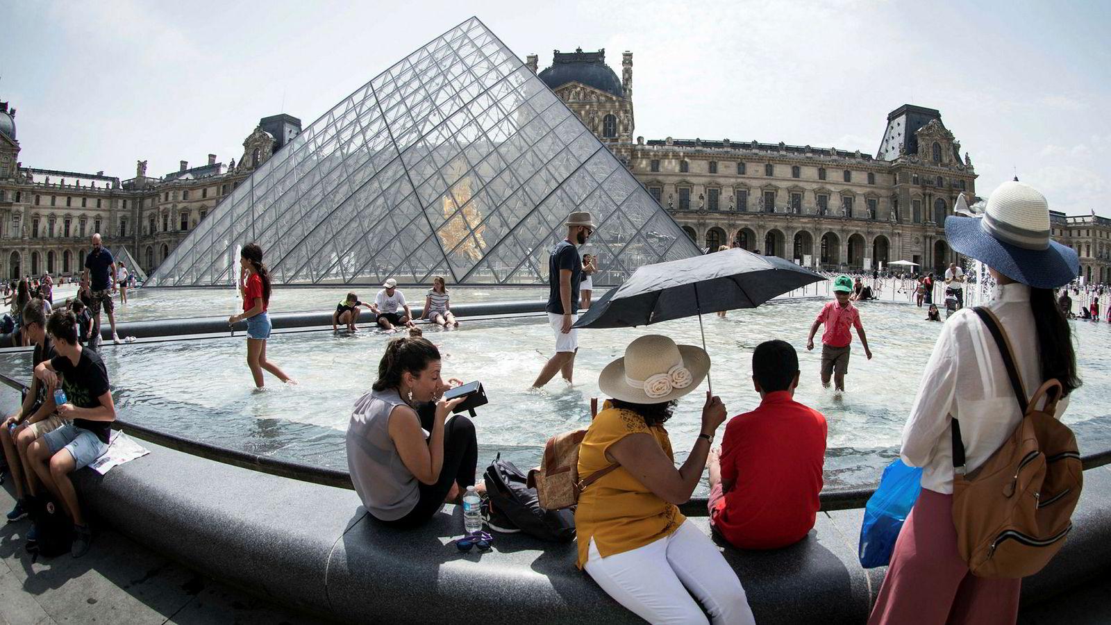Frankrike har målt de høyeste temperaturene siden 2003. Her avkjøler turister seg ved en fontene utenfor Louvre i Paris tirsdag.