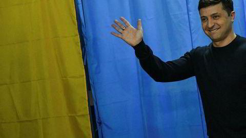 Komiker Volodimir Zelenskij vinker til fotografene på vei inn til stemmeurnen søndag.