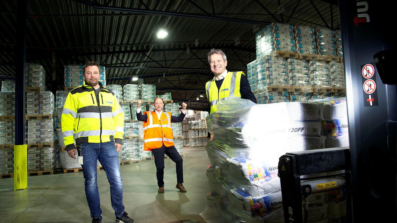 Fabrikklokalene til Mapei er fylt opp med paller med mørtel. Fra venstre: Hovedtillitsvalgt Ole Thomas Norheim i Industri Energi, fungerende NHO-sjef Ole Erik Almlid og Trond Hagerud, administrerende direktør i Mapei i Norden og Baltikum.