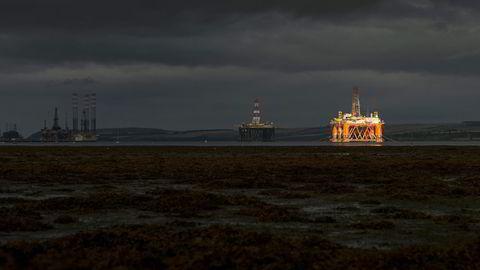 En stripe sol lyser opp en av de ti oljeriggene som ligger i opplag i Cromarty Firth, en fjord på den skotske østkysten
