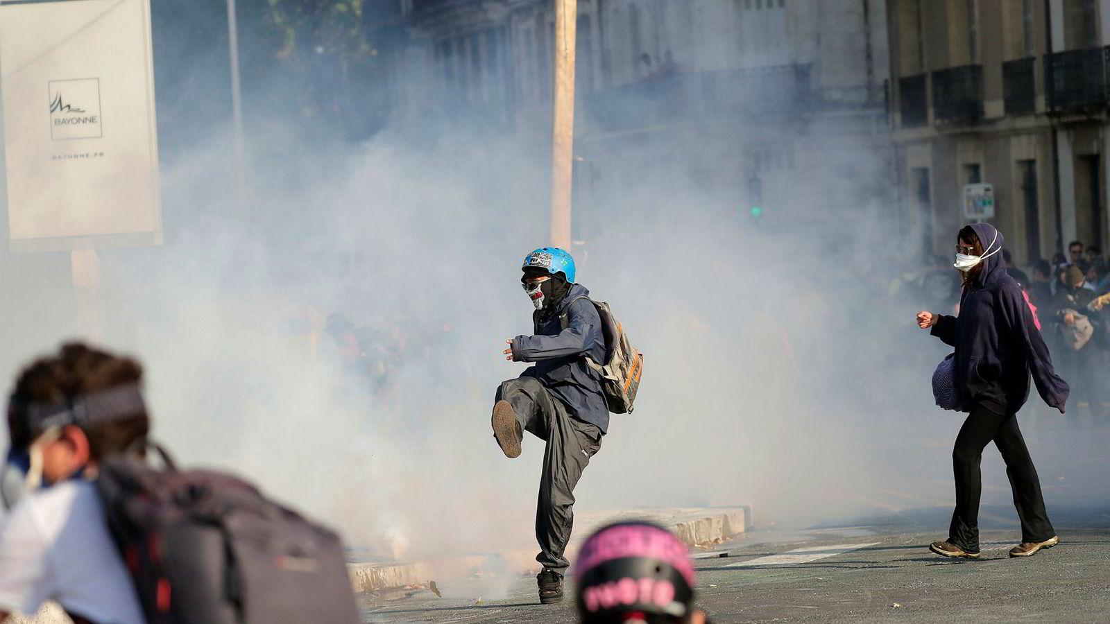 En demonstrant sparker vekk en tåregassflaske kastet av politiet i Bayonne i Frankrike lørdag.
