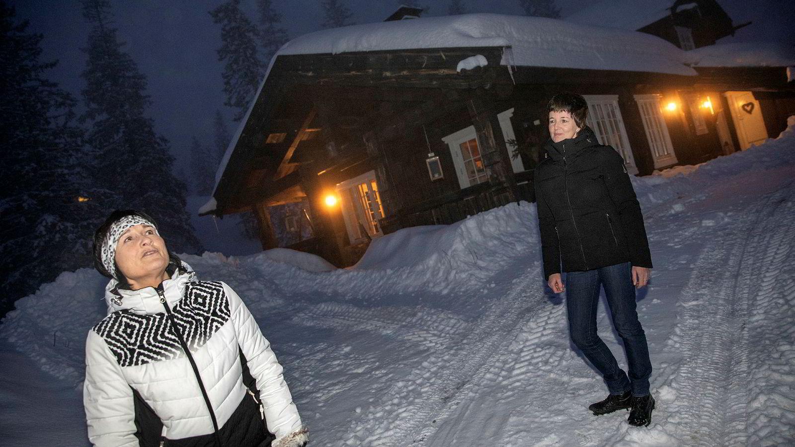 Anne Svenneby (hvit jake) og Hanne-Kjersti Løke er bekymret for om infrastrukturen i Trysil er klar for å ta imot det antall gjester det planlegges for i fremtiden. Her er de fotografert utenfor hytta til Løke.
