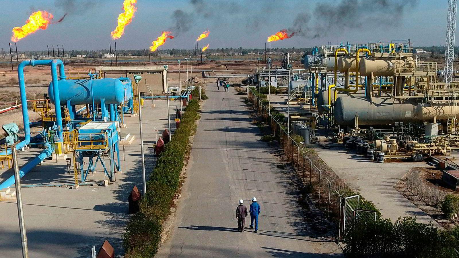 Det internasjonale energibyrået (IEA) nedjusterer prognosene for vekst i global oljeetterspørsel. På bildet ses arbeidere som går langs Nihran Bin Omar-feltet nær Basra i Irak.